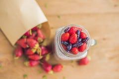 Gezond gelaagd dessert met chiapudding, aardbei en kamperfoelie in een metselaarkruik op rustieke achtergrond royalty-vrije stock foto's