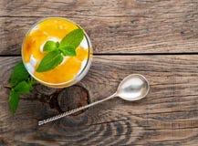 Gezond gelaagd dessert met yoghurt, banaan, mango, cracker op houten achtergrond, hoogste mening royalty-vrije stock fotografie