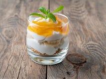 Gezond gelaagd dessert met yoghurt, banaan, mango, koekje op w royalty-vrije stock fotografie