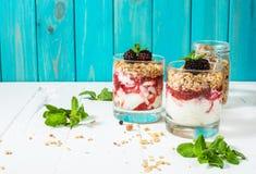 Gezond gelaagd dessert met yoghurt, granola, jam, braambes in glas op houten achtergrond stock afbeeldingen