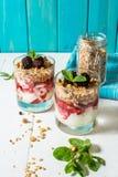 Gezond gelaagd dessert met yoghurt, granola, jam, braambes in glas op houten achtergrond royalty-vrije stock fotografie