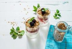 Gezond gelaagd dessert met yoghurt, granola, jam, braambes in glas op houten achtergrond royalty-vrije stock foto