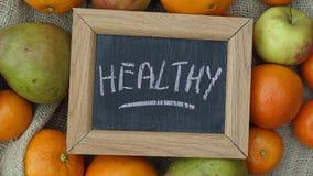Gezond geschreven op een ckaclboard tussen fruit Stock Fotografie