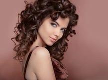 Gezond haar Mooie jonge glimlachende vrouw met lang krullend haar stock foto's