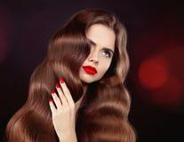 Gezond haar Rode lippen & manicure Golvend haar Mooie modelgi stock afbeelding