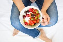 Gezond het Eten Concept Vrouwen` s handen die kom met muesli, yoghurt, aardbei en kers houden Hoogste mening levensstijl royalty-vrije stock foto's