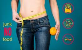 Gezond het eten, dieet en geschiktheidsconcept Geen ongezonde kost Gezond vrouwelijk lichaam met oranje en metende band Stock Foto
