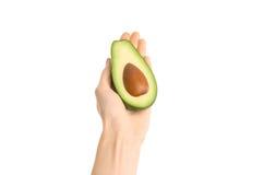 Gezond het eten en dieetonderwerp: Menselijke hand die een halve die avocado houden op een witte achtergrond in de studio wordt g Stock Foto's