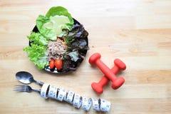 Gezond het eten en geschiktheidsconcept, Hoogste mening van Plantaardige salade met dumbells en het meten van band op houten donk royalty-vrije stock foto
