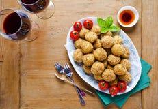 Gezond Italiaans voorgerecht met arancini van risottoballen, groene ol stock fotografie