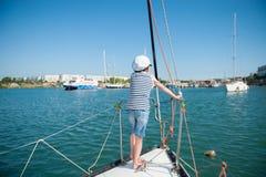 Gezond jong geitje in kapiteinshoed die zich op de raad van het luxejacht in zeehaven in de zomer bevinden royalty-vrije stock afbeelding