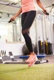 Gezond jong vrouwentouwtjespringen in een gymnastiek, gewas stock fotografie