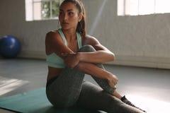 Gezond jong wijfje die rust na opleiding in gymnastiek nemen stock afbeelding