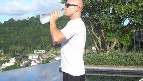 Gezond knap mensen drinkwater van de fles terwijl status op een zwembad van de dakoneindigheid stock footage