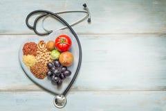 Gezond levensstijl en gezondheidszorgconcept met voedsel, hart en stethoscoop Stock Afbeeldingen