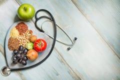 Gezond levensstijl en gezondheidszorgconcept met voedsel, hart en stethoscoop stock foto