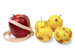 Gezond levensstijlconcept Een grote contant geldappel met een metende band en gele kleine bedorven appelen royalty-vrije stock afbeeldingen