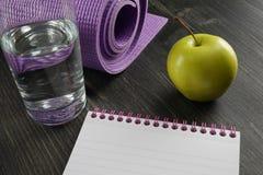 Gezond levensstijlconcept - water, appel, notitieboekje en yogamat stock afbeelding