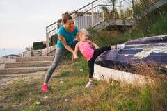Gezond moeder en babymeisje die zich in openlucht uitrekken Royalty-vrije Stock Afbeelding
