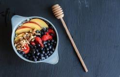 Gezond ontbijt in blauwe kom met van de fruitbovenste laagjes en honing sti Stock Foto's