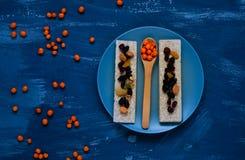Gezond ontbijt, graangewas, dieetbrood op blauwe achtergrond, duindoorn in een houten lepel, close-up, natuurlijke lichte, hoogst Stock Fotografie