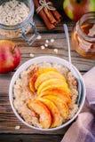 Gezond ontbijt: havermeelkom met gekarameliseerde perziken, kaneel en honing Royalty-vrije Stock Foto's