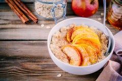 Gezond ontbijt: havermeelkom met gekarameliseerde perziken, kaneel en honing Royalty-vrije Stock Afbeelding