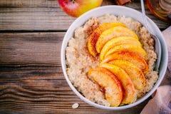 Gezond ontbijt: havermeelkom met gekarameliseerde perziken, kaneel en honing Stock Afbeeldingen