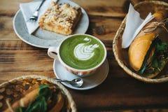Gezond ontbijt in het restaurant: kop van groene thee met melk, dessert en sandwiches met groenten en kruiden  Royalty-vrije Stock Afbeelding