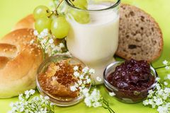 Gezond ontbijt met broodje, brood, honing, jam, glas vergiste melk en uiterst kleine bloemen Stock Foto's