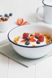 Gezond ontbijt met graangewassen en bessen in een emailkom Stock Afbeelding