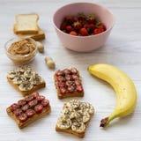 Gezond ontbijt met ingrediënten, het op dieet zijn concept Veganisttoosts met vruchten, zaden, pindakaas op witte houten achtergr royalty-vrije stock afbeelding