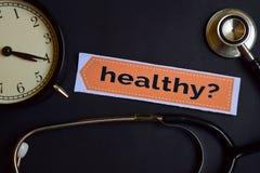 Gezond? op het drukdocument met de Inspiratie van het Gezondheidszorgconcept wekker, Zwarte stethoscoop stock afbeeldingen