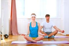 Gezond paar dat yoga thuis doet Stock Afbeeldingen