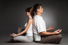 Gezond paar in yogapositie inzake dark Stock Afbeelding