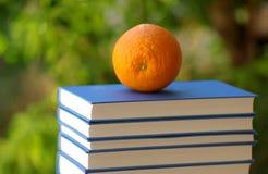 Gezond sinaasappel en boek royalty-vrije stock afbeeldingen