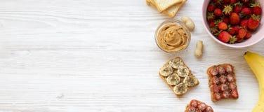 Gezond vegetarisch ontbijt met ingrediënten, dieetconcept Veganisttoosts met vruchten, zaden, pindakaas op een houten wit stock afbeelding