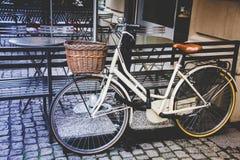 Gezond vervoerconcept De uitstekende fiets ging dichtbij koffie met oude houten mand in Italië, Milaan weg Mistig dalingseiland stock fotografie