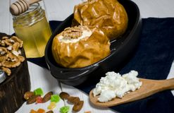 Gezond voedsel De gebakken appelen met kwark en de noten liggen in een zwarte bakselschotel op een witte houten lijst royalty-vrije stock foto