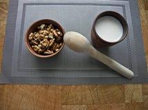 Gezond voedsel in een bruine kleischotel met een houten lepel op een tafelkleed over een grijs tafelkleed stock foto