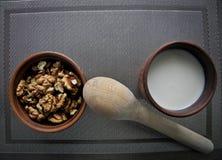 Gezond voedsel in een bruine kleischotel met een houten lepel op een tafelkleed over een grijs tafelkleed royalty-vrije stock foto