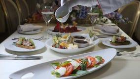 Gezond voedsel en vegetarisch concept Sluit omhoog van het gieten van olijfolie over caprese salade Italiaanse caprese salade met stock footage