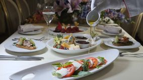 Gezond voedsel en vegetarisch concept Sluit omhoog van het gieten van olijfolie over caprese salade Italiaanse caprese salade met stock videobeelden