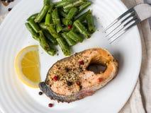 Gezond voedsel Gebakken rode vissen, roze zalm, zalm en slabonen met een plak van citroen op een plaat Stock Foto's
