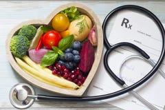 Gezond voedsel in hartstethoscoop en medisch voorschriftdieet en geneeskundeconcept stock afbeelding