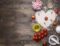 Gezond voedsel, het koken en conceptenrisotto met ham, olie, kersentomaten, rijst betegeld hart, de grens van de valentijnskaarte Royalty-vrije Stock Foto's