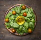 Gezond voedsel, het koken en vegetarische concepteningrediënten voor de salade, verse die spinaziebladeren, kersentomaten, op a w Stock Foto