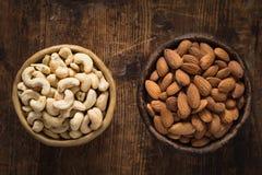 Gezond voedsel: kom van cachou en amandelen op houten lijst Stock Foto's