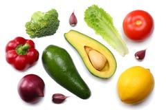 Gezond voedsel mengeling van avocado, citroen, tomaat, rode ui, knoflook, zoete die groene paprika en rucolabladeren op witte ach Stock Afbeelding