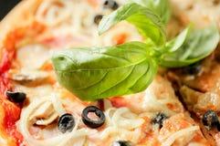 Gezond voedsel Sluit omhoog voedselbeeld van basilicum op Italiaanse pizza Macro fotografie Het eten van achtergrond stock afbeelding